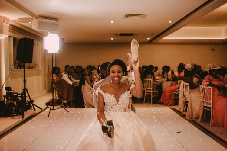 bride holds up shoe in froyle park wedding reception