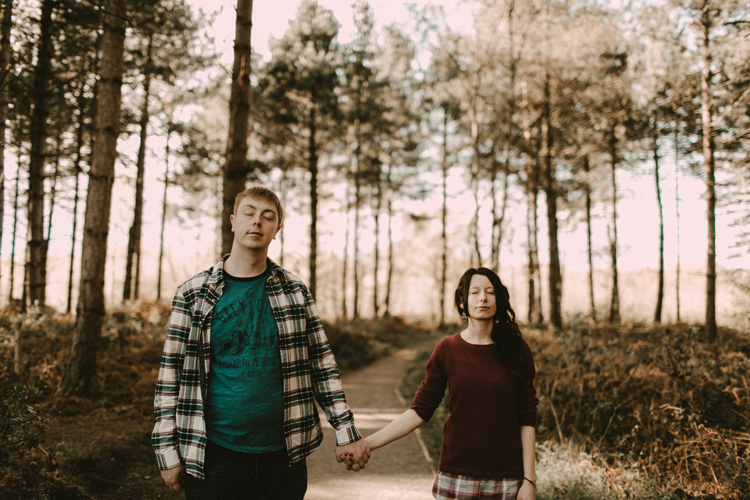 couple hold hands and close eyes in birchington forest engagement session