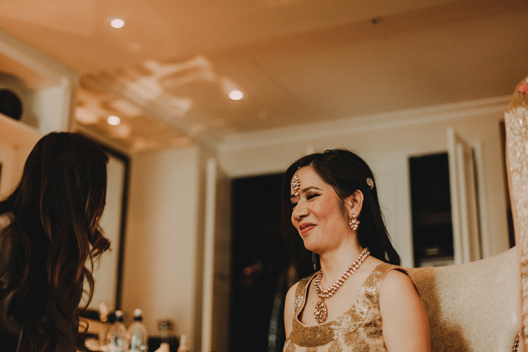 asian bride smiles whilst getting ready for hindu wedding ceremony