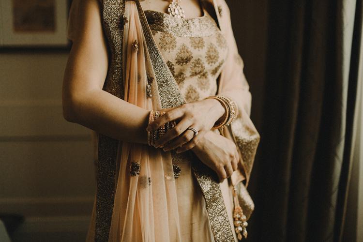 asian bride adjusts bracelet before traditional hindu ceremony