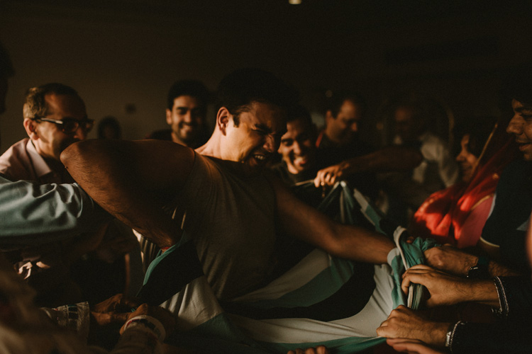 groomsmen tearing grooms clothes during ritual in hindu puja