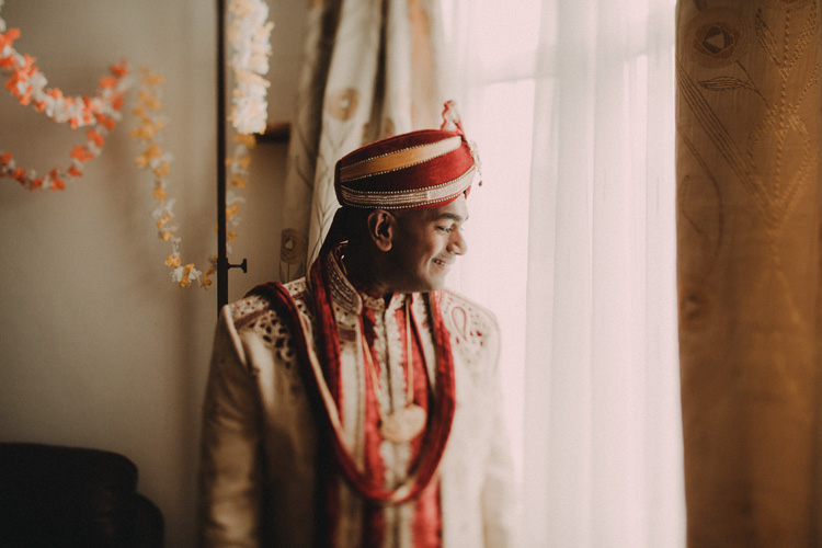 groom looks out window ready for his hindu ceremony