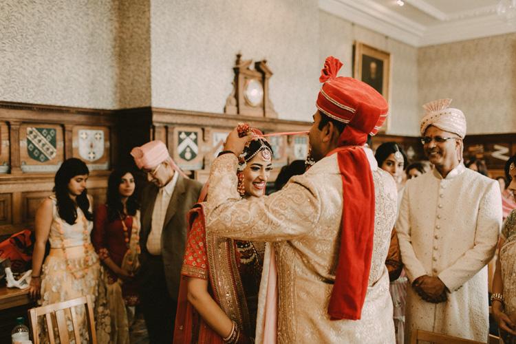 indian groom places flower garland around brides neck in hindu wedding