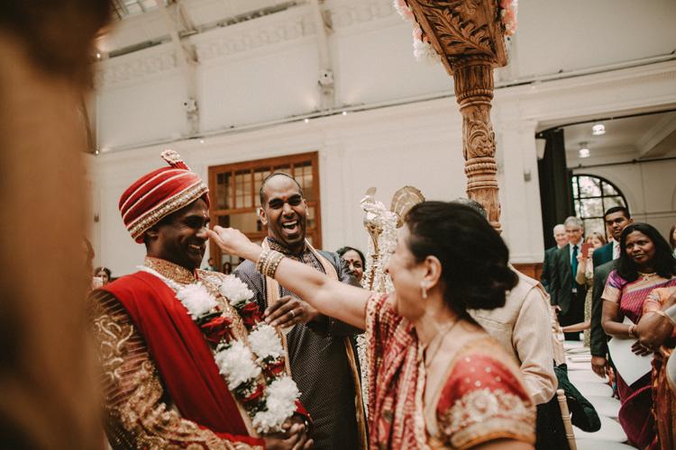 grooms mother jokes with groom before entering the mandap in london hindu wedding