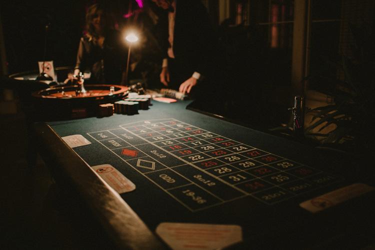 card dealer deals card during poker game in syon park wedding reception
