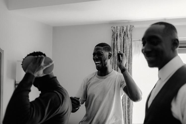 groomsmen share jokes whilst getting ready for froyle park wedding