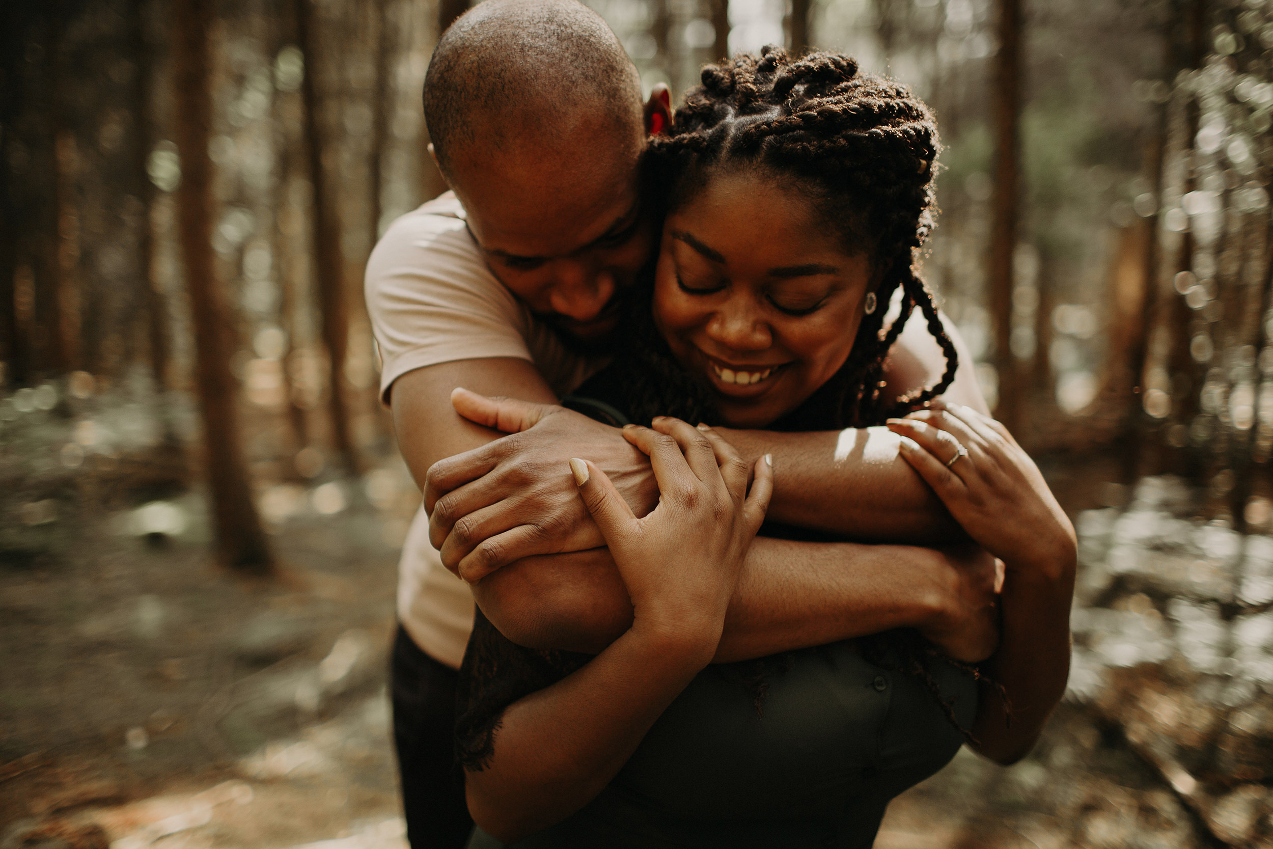 engaged couple hug each other intimately in the black park