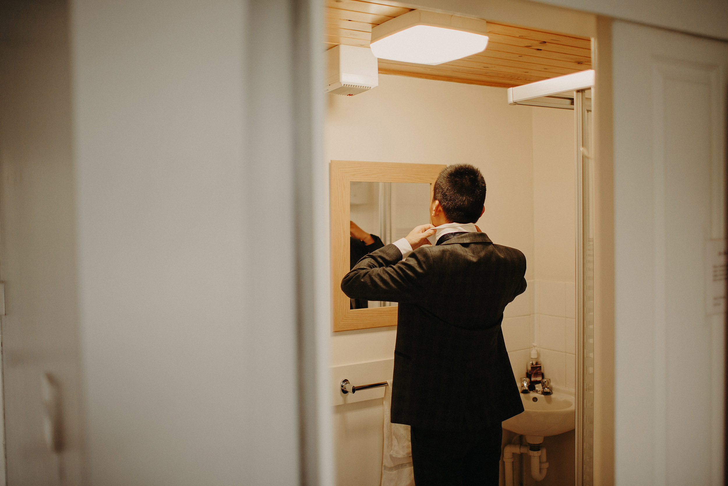 tattooed groom getting ready during scottish elopement