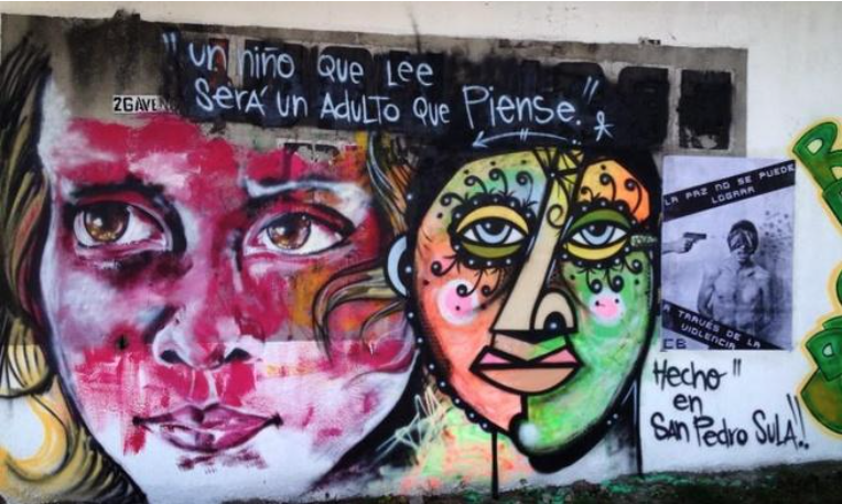 """This graffiti mural reads: """"A child that reads will be an adult that thinks."""" The small black and white image to the right reads: """"Peace cannot be achieved through violence.""""[1]"""