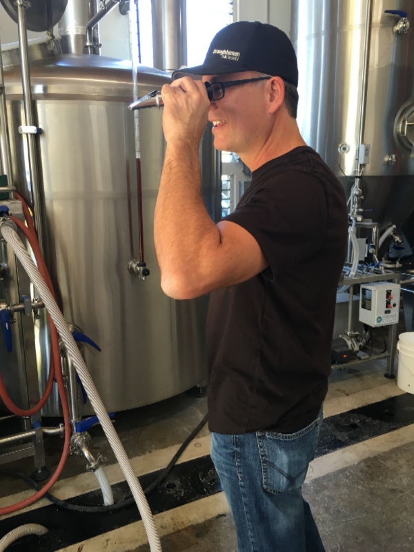 Kris checking the wort's sugar content with a refractometer.