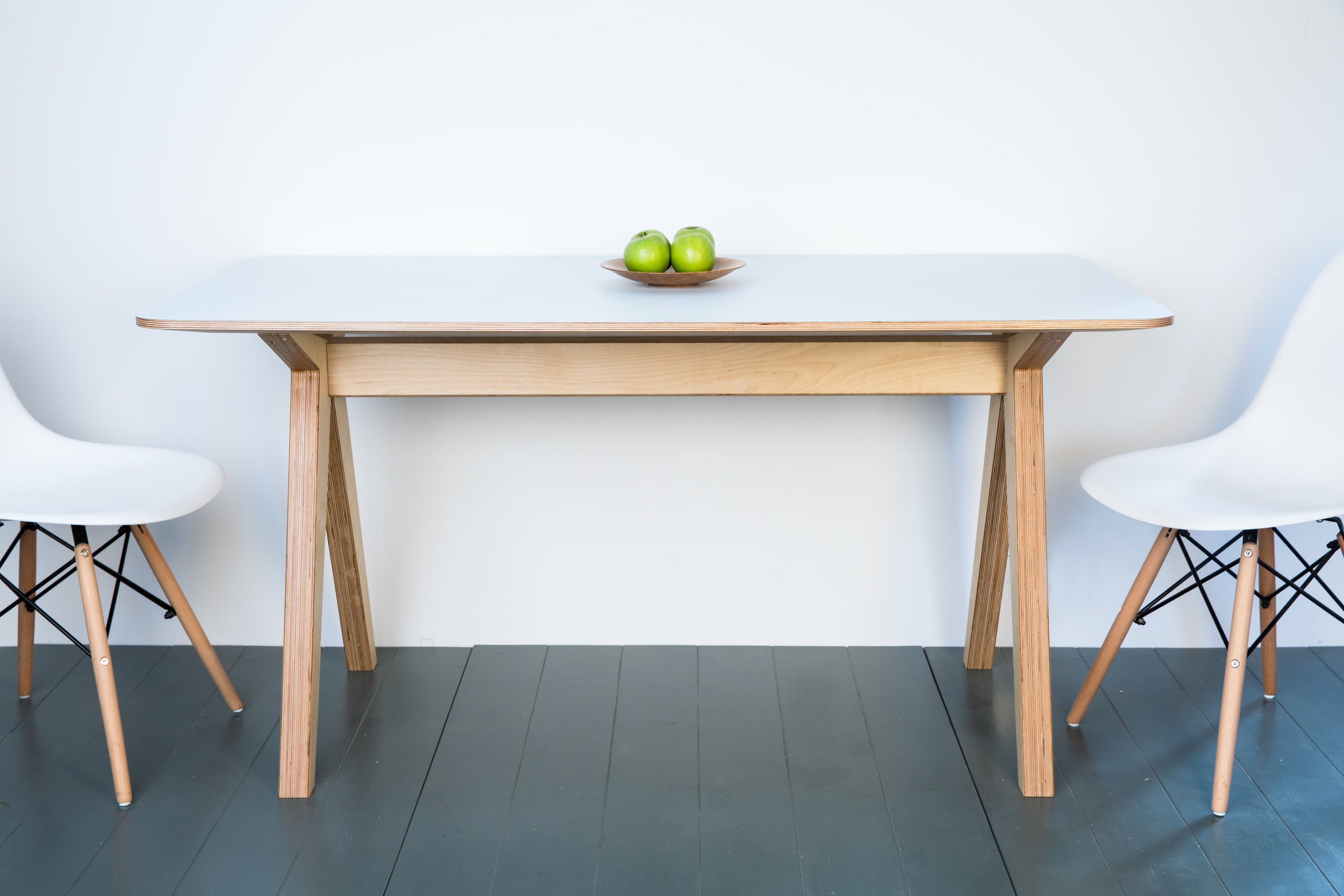 Kitchen trestle table in birch ply with a formica surface. This table is available in a colour of your choice and can be built to your exact size requirements.  material: birch ply, formica  dimensions as shown: l 1500 h 750 d 800  please contact for pricing
