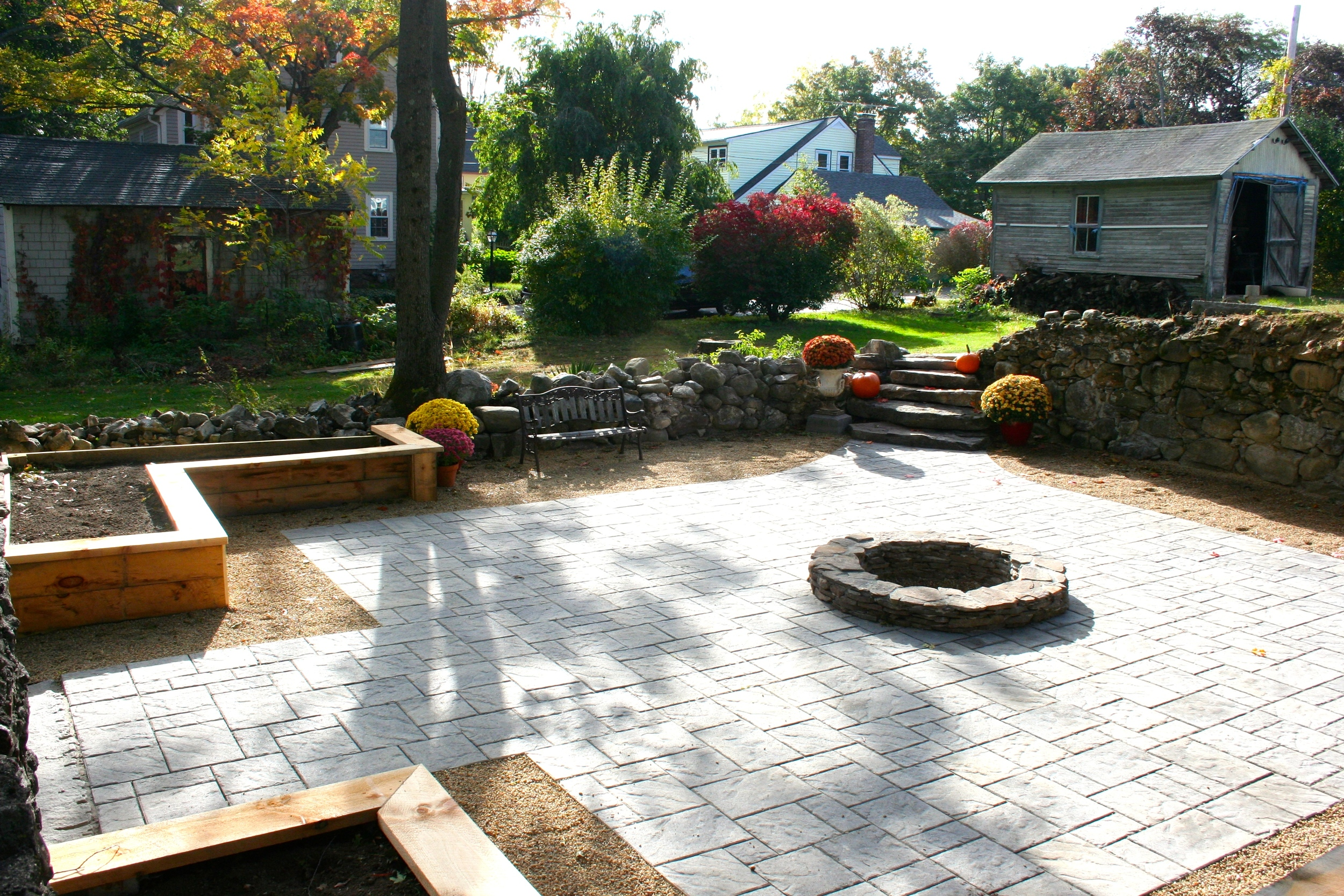 The foundation from a long-gone barn becomes an outdoor gathering area with built-in fire pit. We added natural stone stairs in one corner to easily access the house. Corner raised beds for growing flowers and vegetables help frame the design and provide seasonal interest.