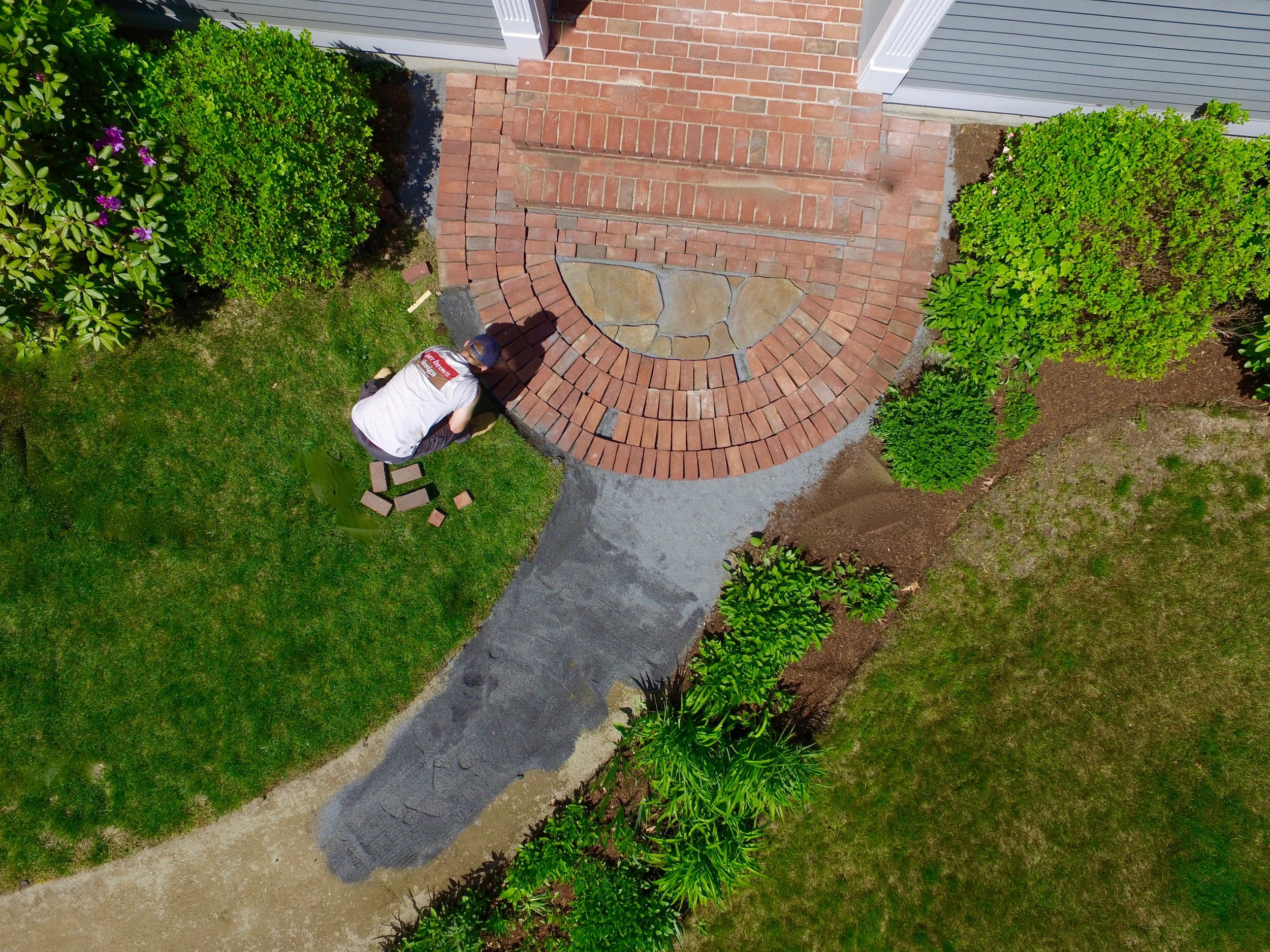 An old brick walkway was meticulously restored when its original bed had become uneven and unsafe.