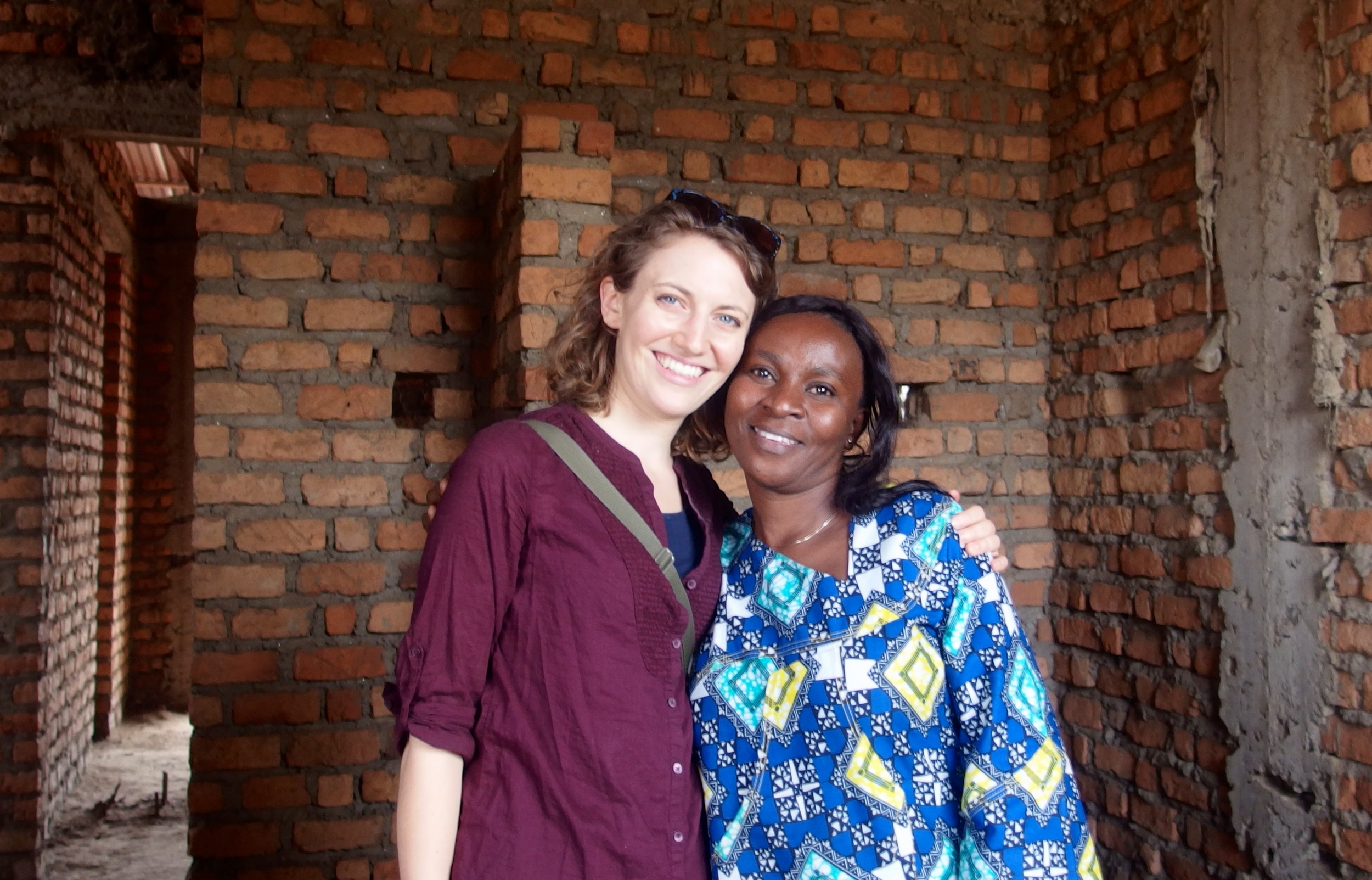 Mwendo Congo representative, Amy, with Interim Secretary General of Let Africa Live during site visit in August 2015. They stand together in one of ten unfinished rooms. With your support, this room will house two students and their children.