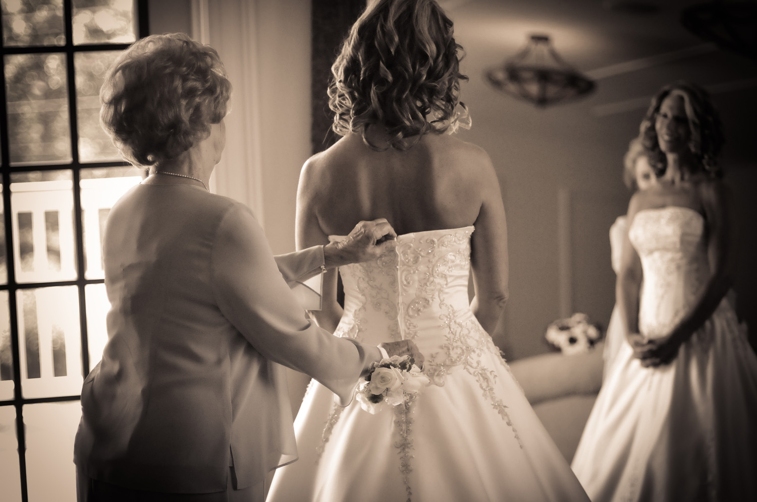 lacing up bride's gown at Carriage House / Meyer Photography