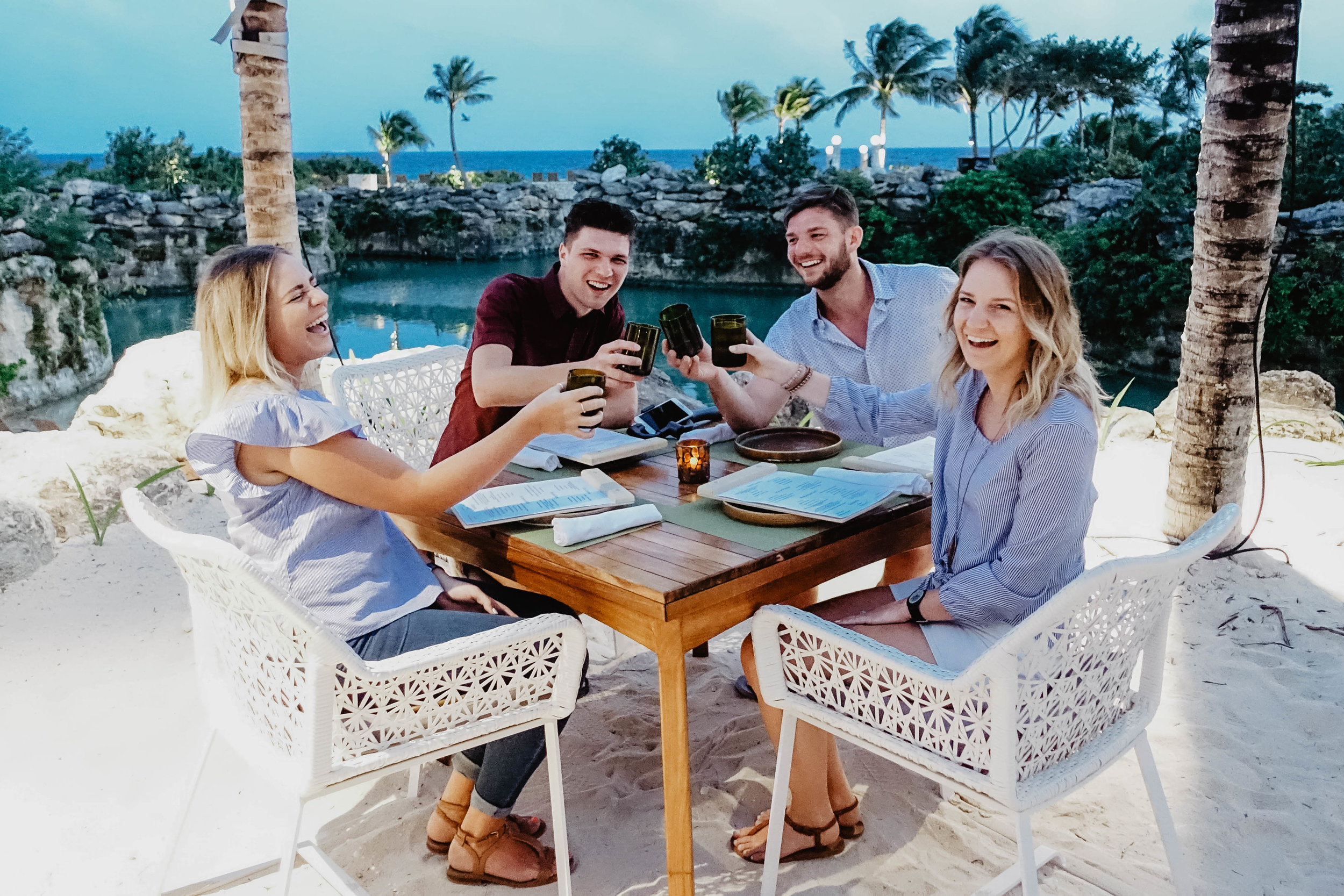 Four friends toasting to their last night in Mexico. View looking out over the ocean.