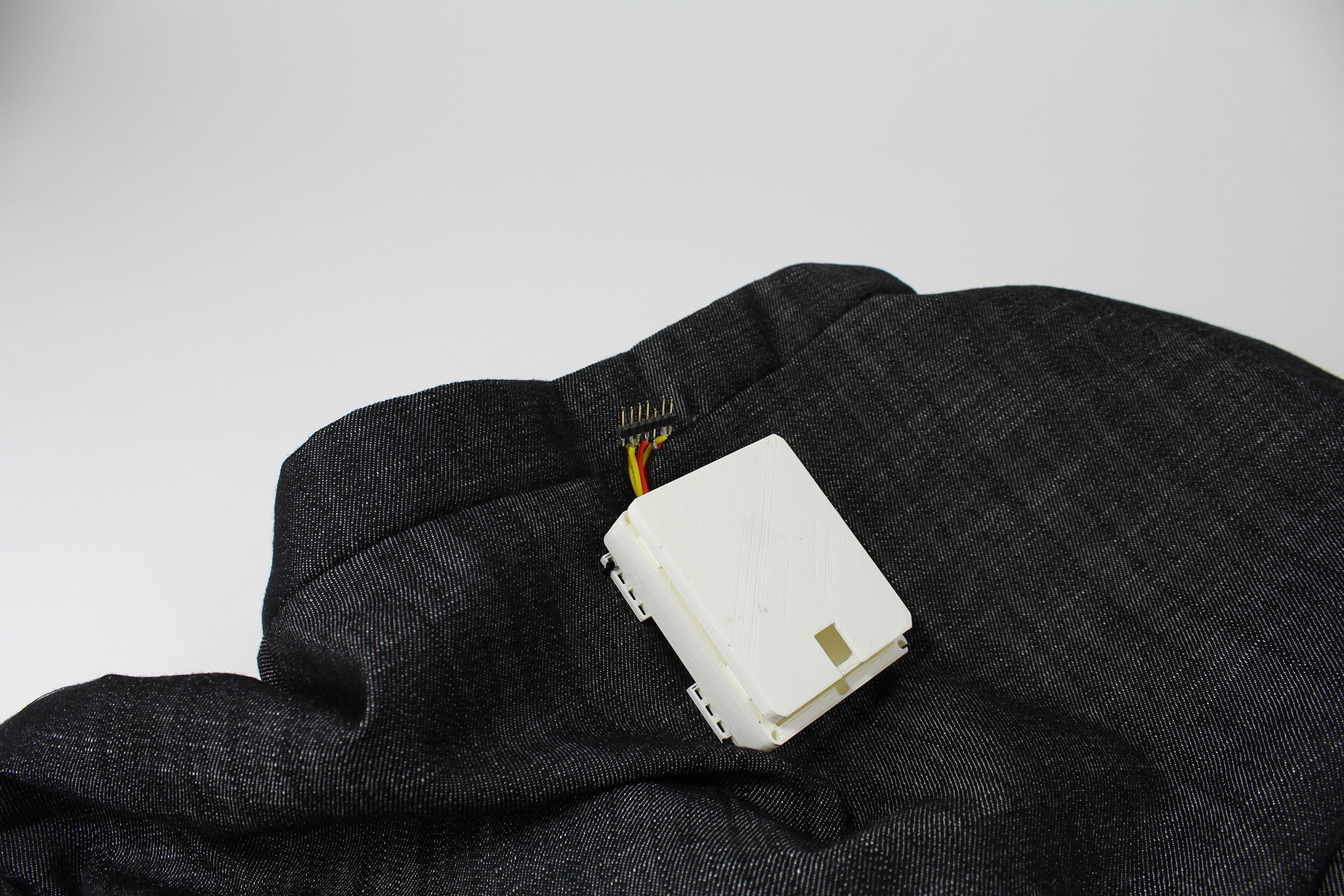 Arduino micro controller and battery housed in 3D printed case sewn onto the upper back.