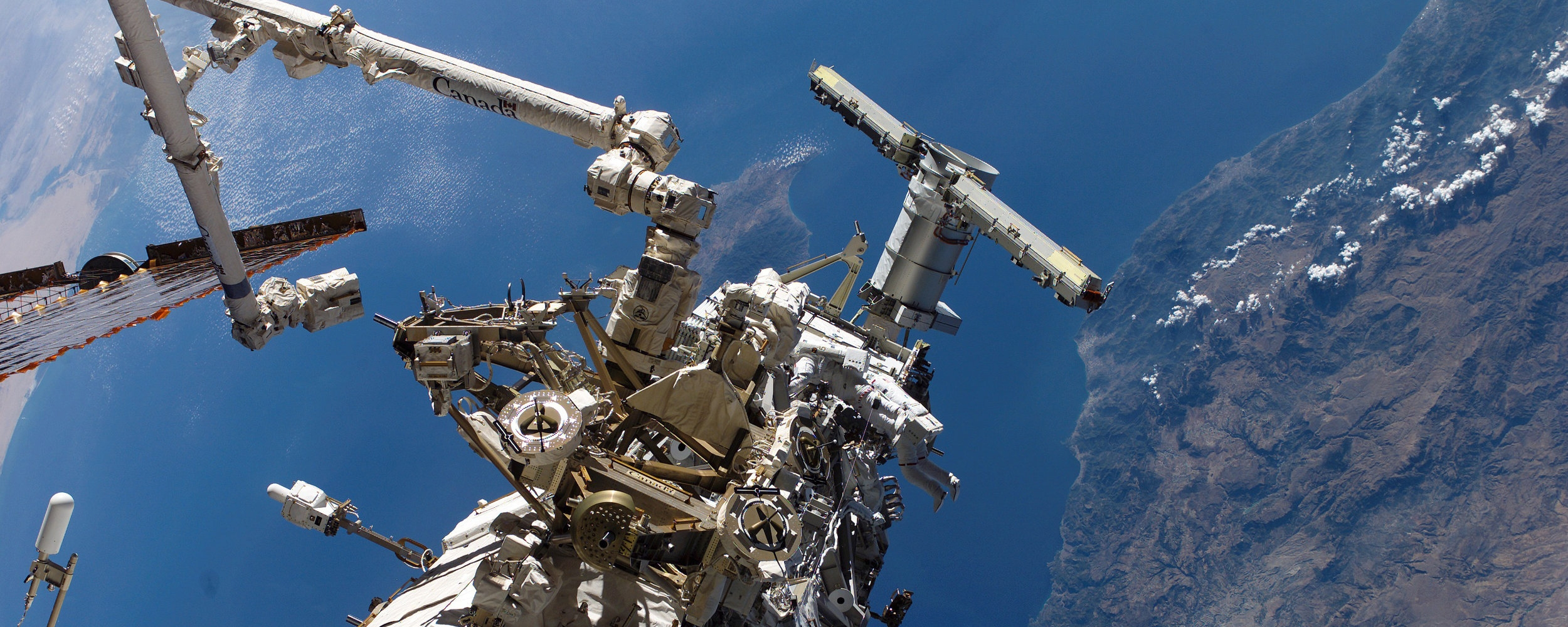 Astronauts perform a space walk on the International Space Station.