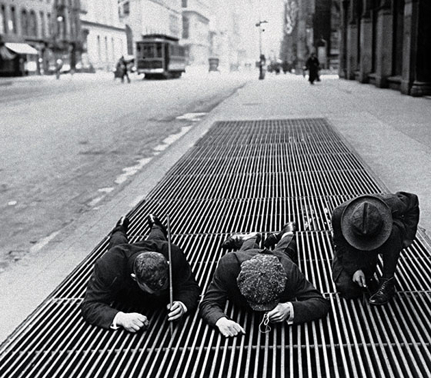 historicaltimes :     3 boys fish for change in the street grates during the depression. N.Y.C. 1930