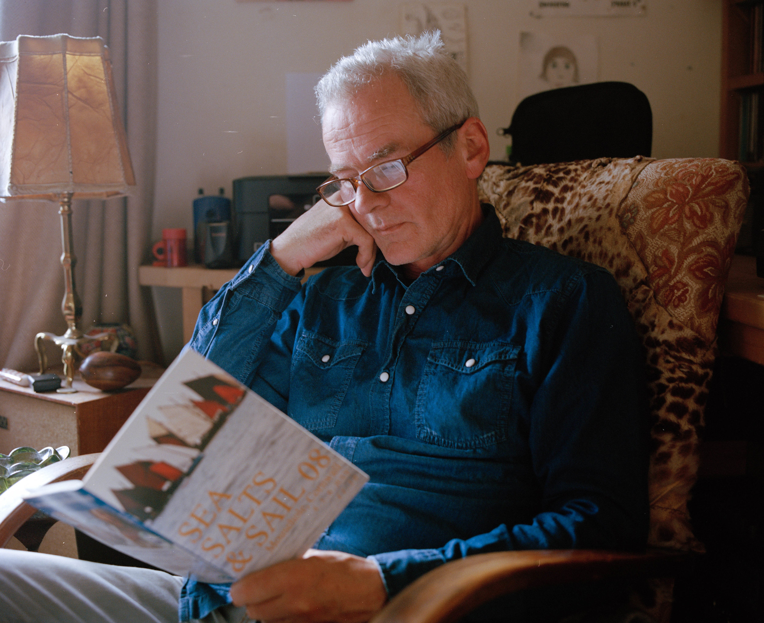 """Neil reading a leaflet in his house. Neil says """" I think that success is having a family around you, you don't need more than that really."""""""