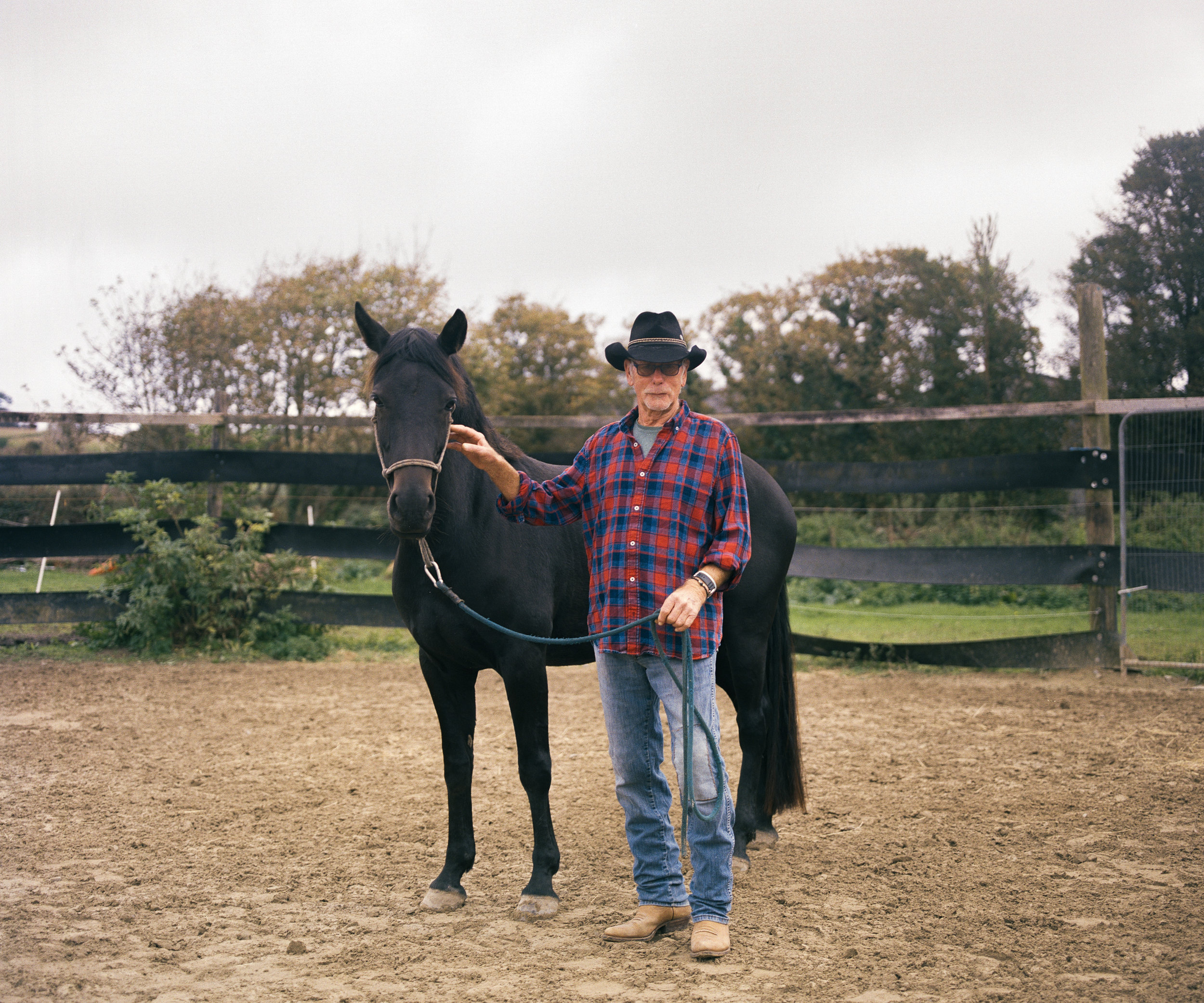 A portrait of western rider Dave Swift, standing next to his horse in his riding ring. Dave first discovered western riding when he was 19 when he Travelled to the U.S to Nevada to work as a ranch hand for a year, gaining a deeper insight into being a working cowboy.