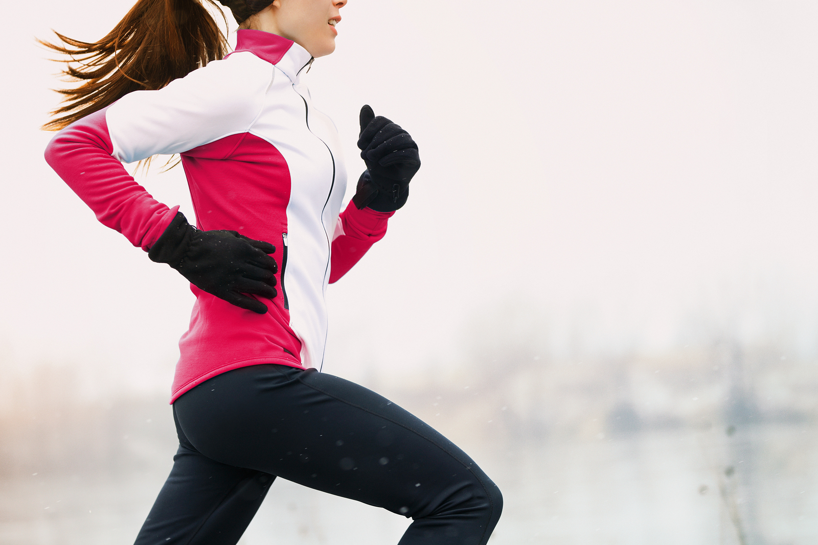 Winter running athlete woman on cold run jogging fast with speed