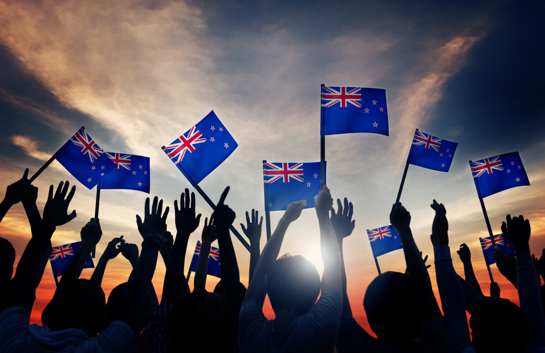 Silhouettes of People Holding Flag of New Zealand