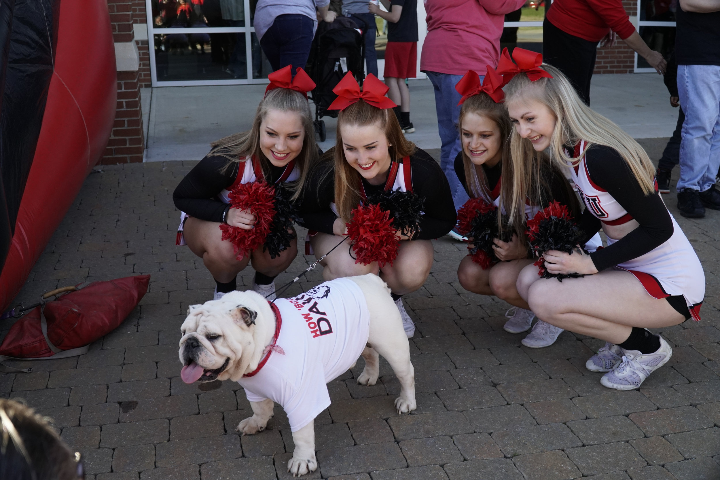 Cheerleaders posing for a photo with Roebuck.