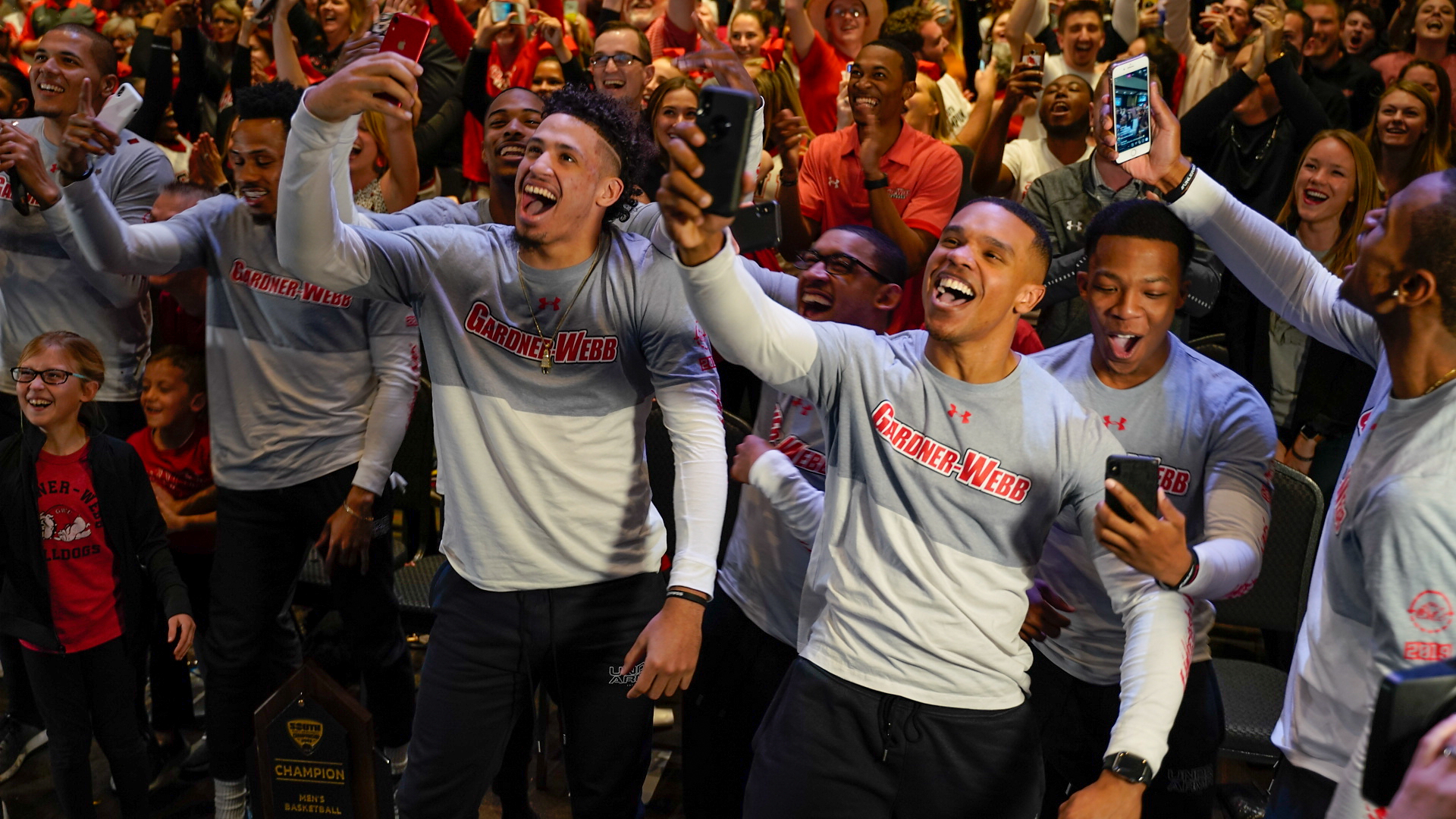 Basketball players celebrating as it's announced that they will face UVA.