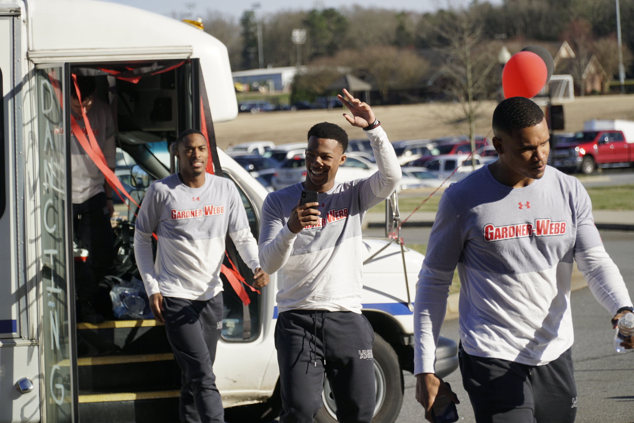 Basketball players exit the bus that dropped them off at the Tucker Student Center.