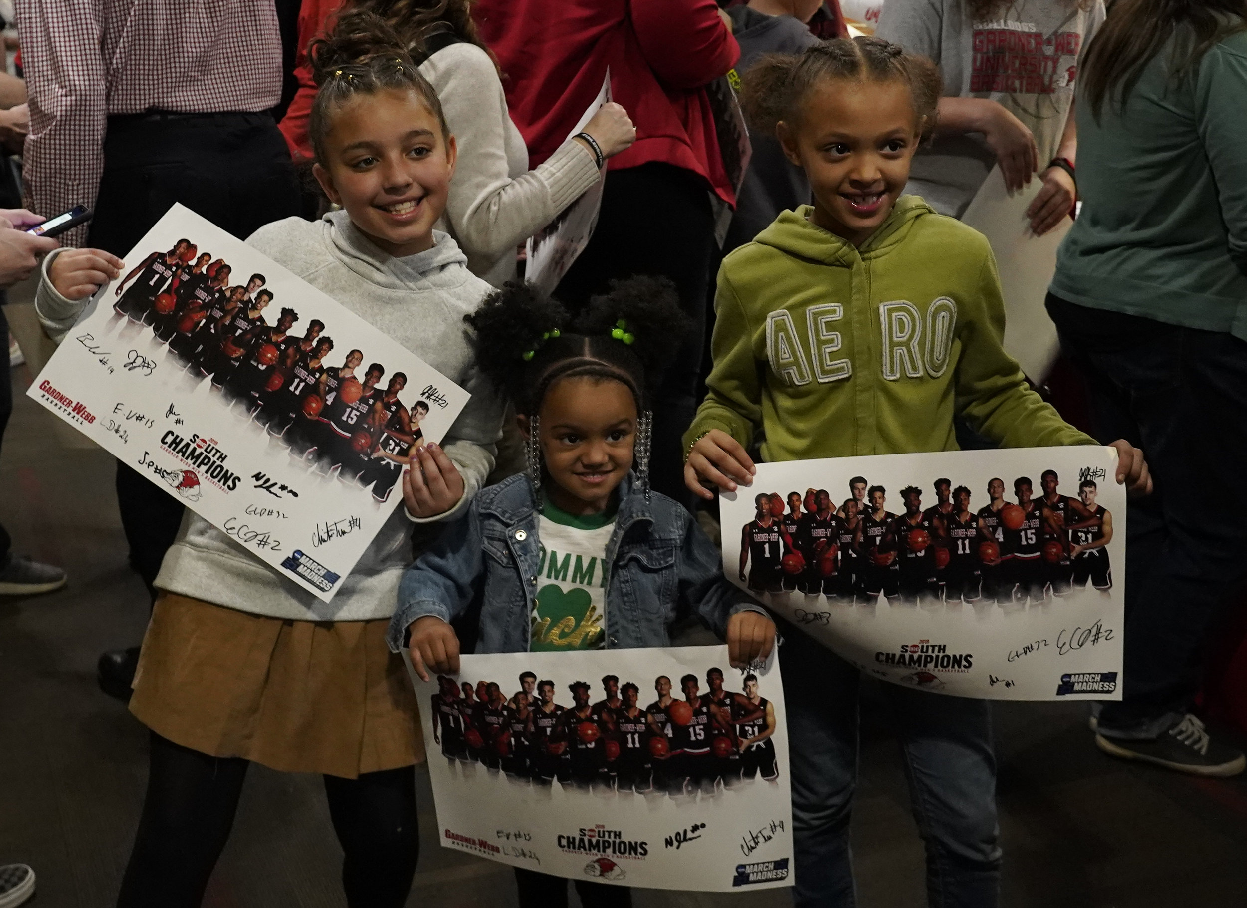 Children post with posterns that the team autographed.