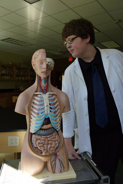 Damnian posing with an anatomical model. As a Summer Scholar, he conducted original research and completed a research project on a topic of his choosing.