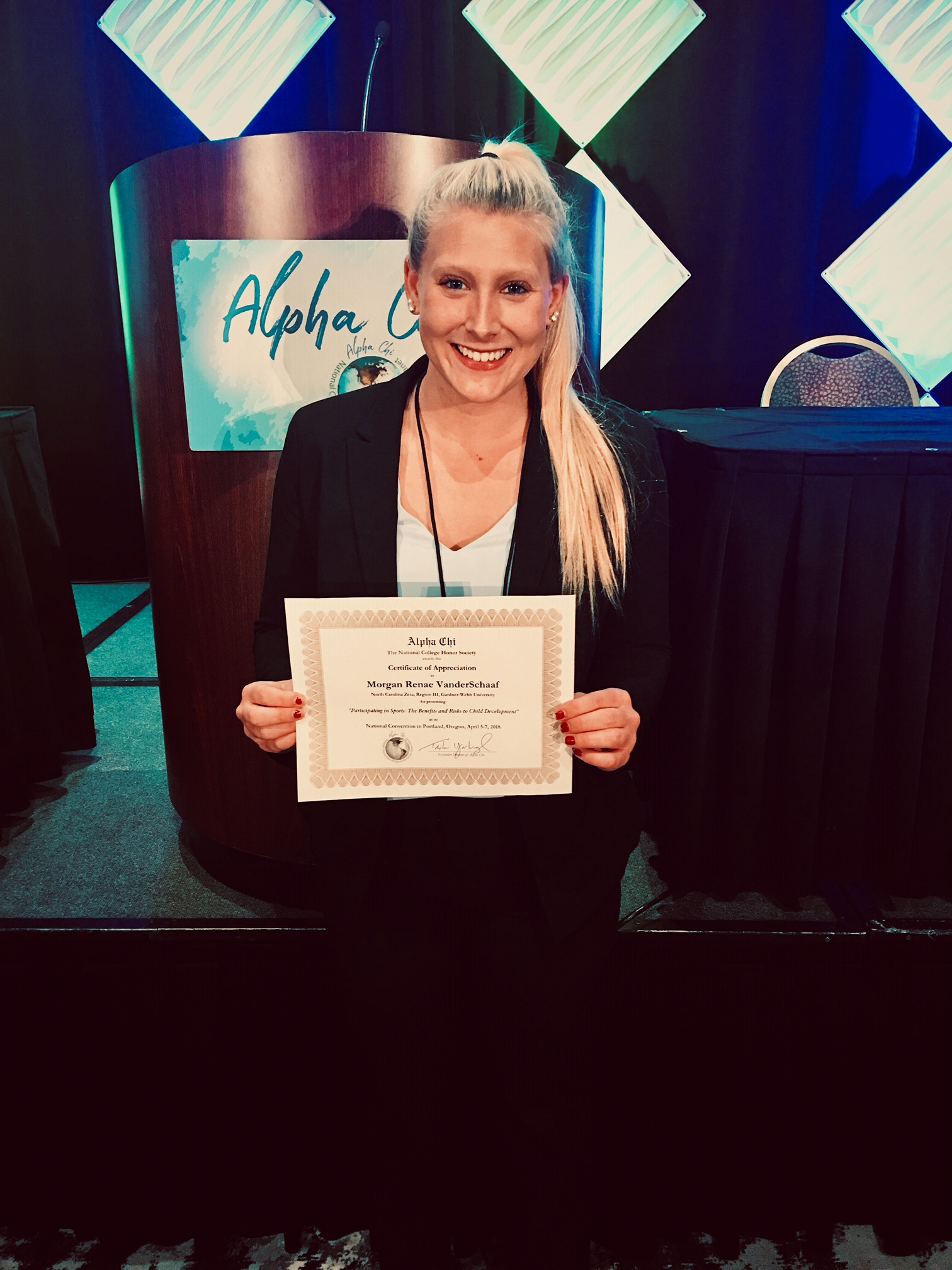 Morgan at the Alpha Chi National Conference in Cleveland, Ohio, posing with her certificate of appreciation for presenting her research project.