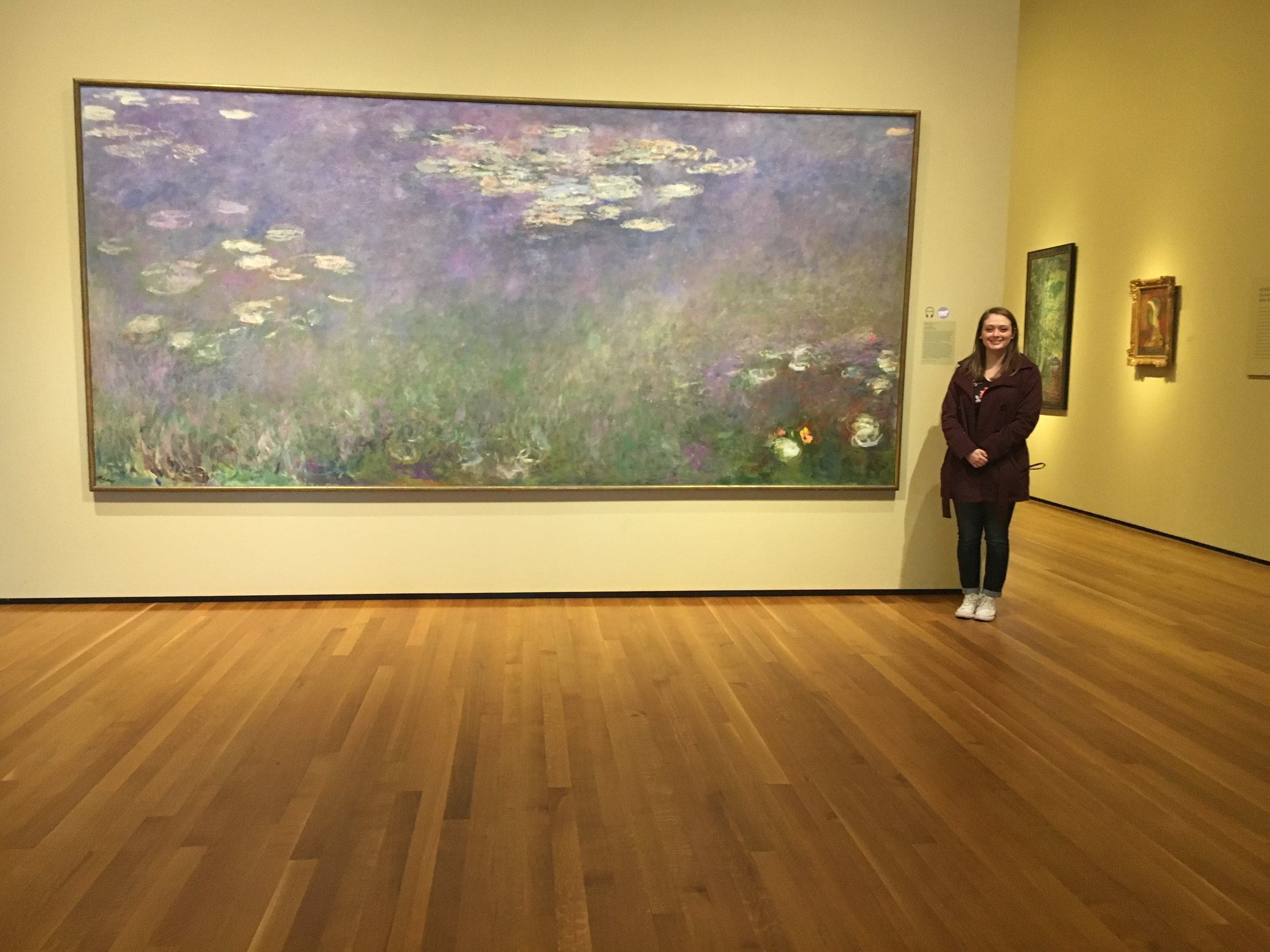 Sydney posing in front of artist Claude Monet's  Water Lillies  painting during her trip to Cleveland, Ohio for the 2019 Alpha Chi National Conference.