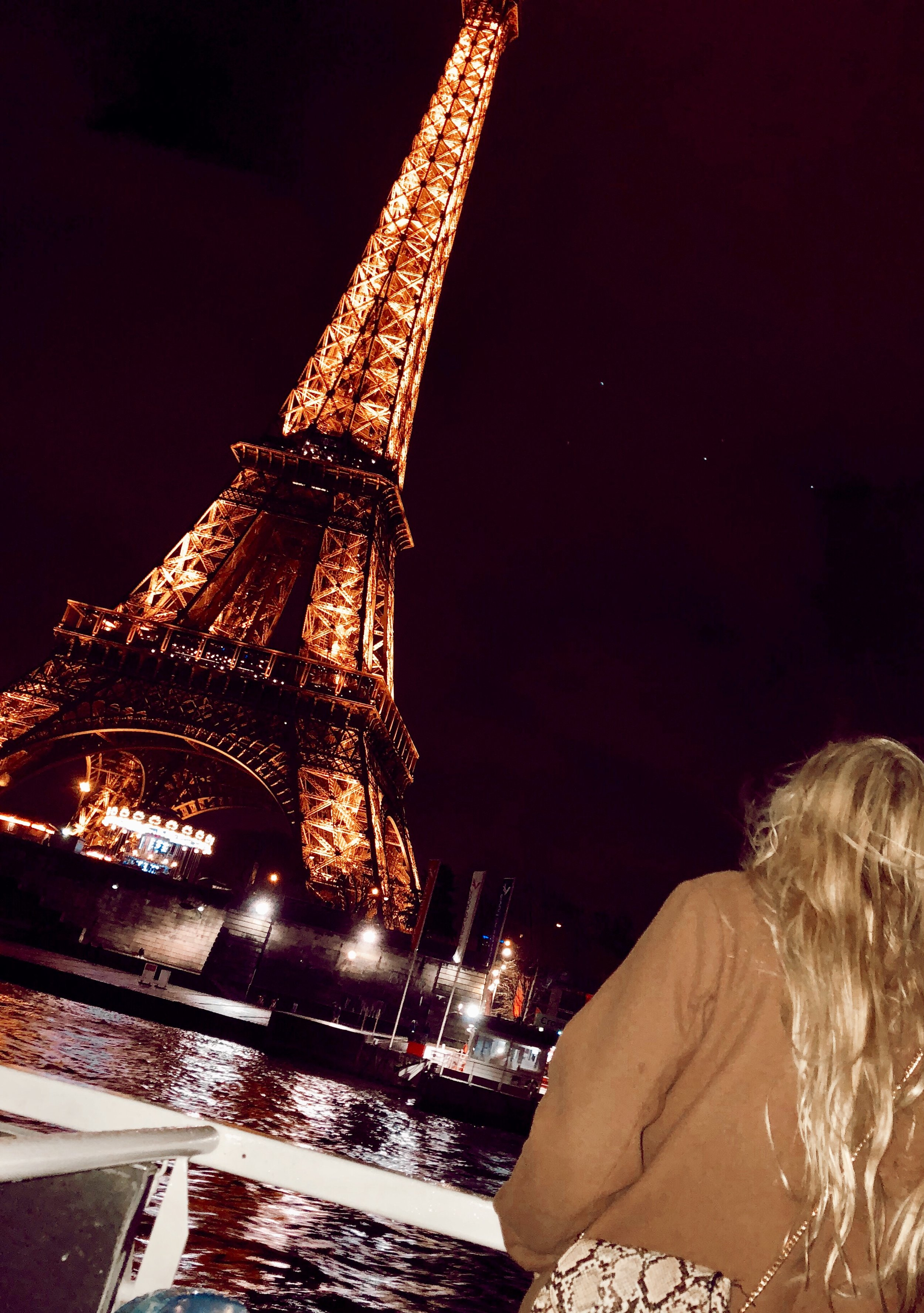 Miranda in front of the Eiffel Tower at night.