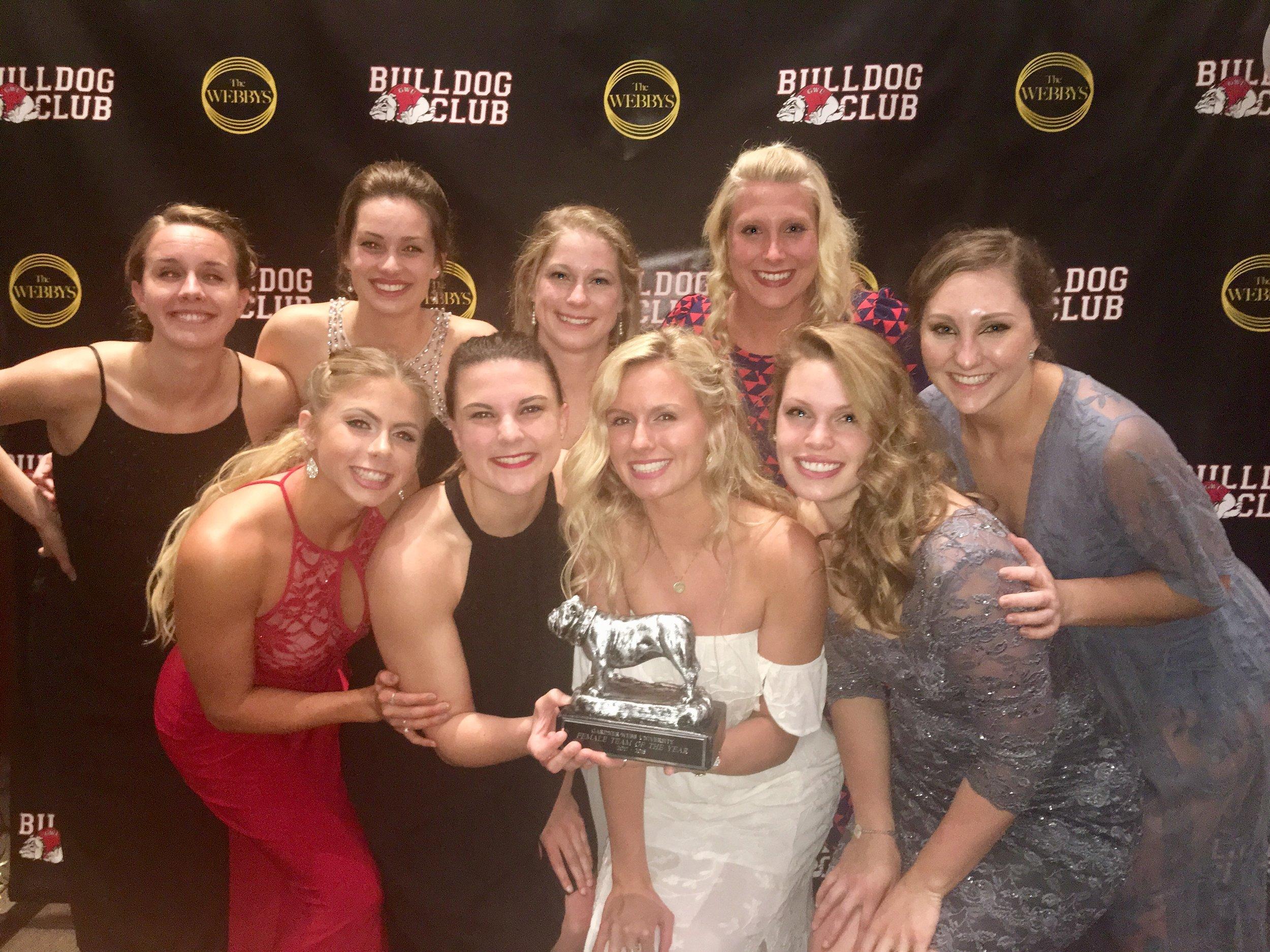 Members of the women's swim team holding up their Bulldog award.