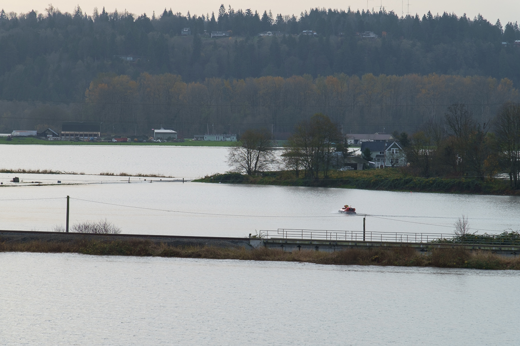 A rescue hovercraft crosses flooded farm fields and roads to check on residents stranded during the flood.