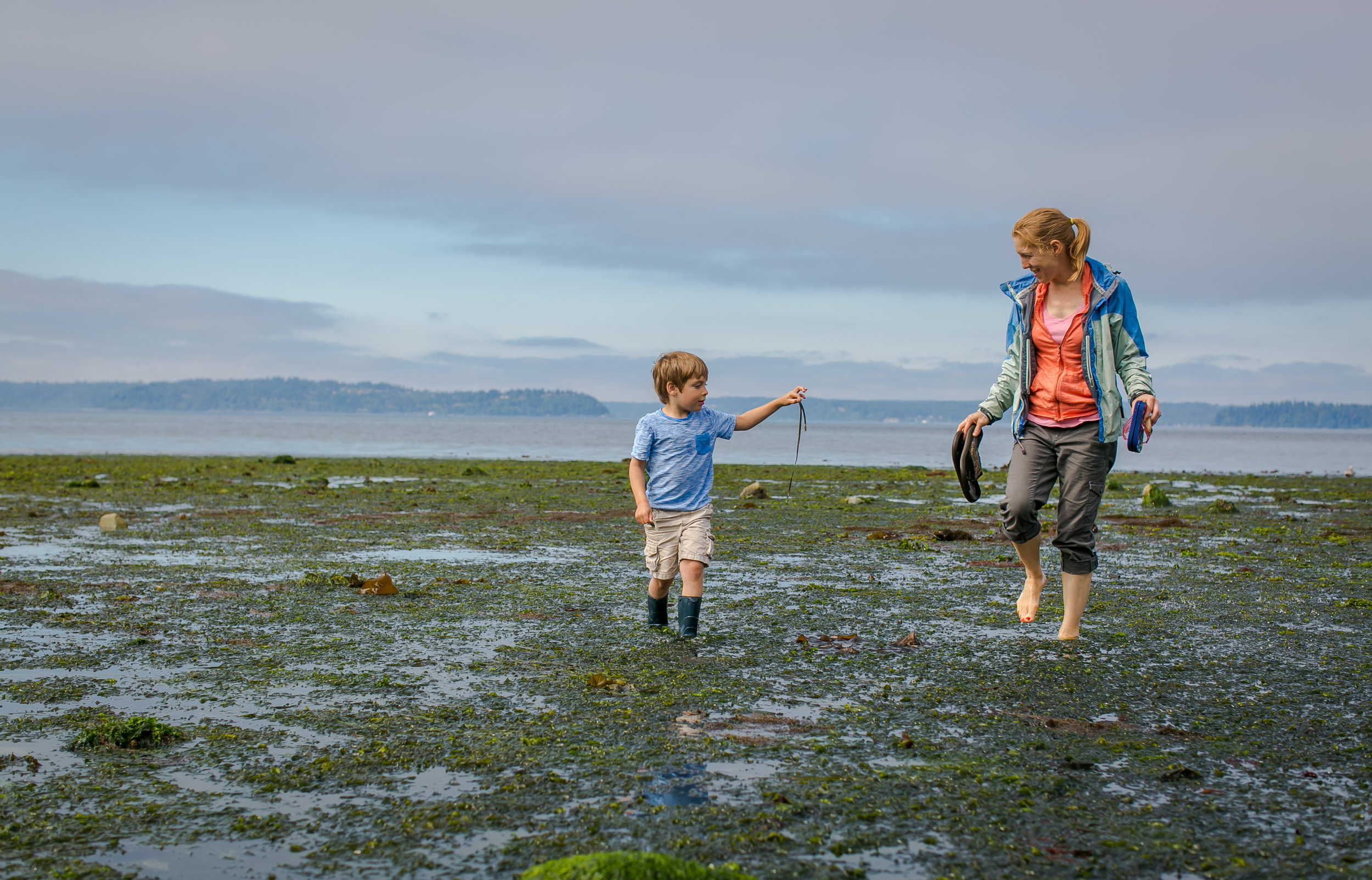 A child plays in the low tide on Alki Beach in West Seattle. (Photo ©Paul Joseph Brown)