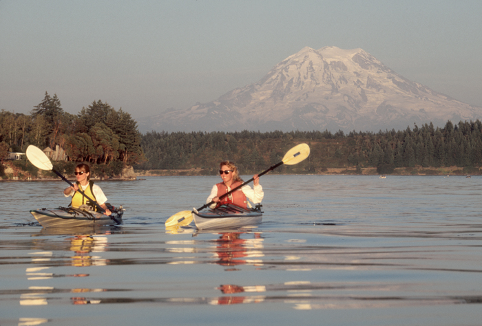 Sea kayakers in Puget Sound, Mount Rainier in the background. Two women paddle off the Nisqually Reach. Photo by Joel Rogers.