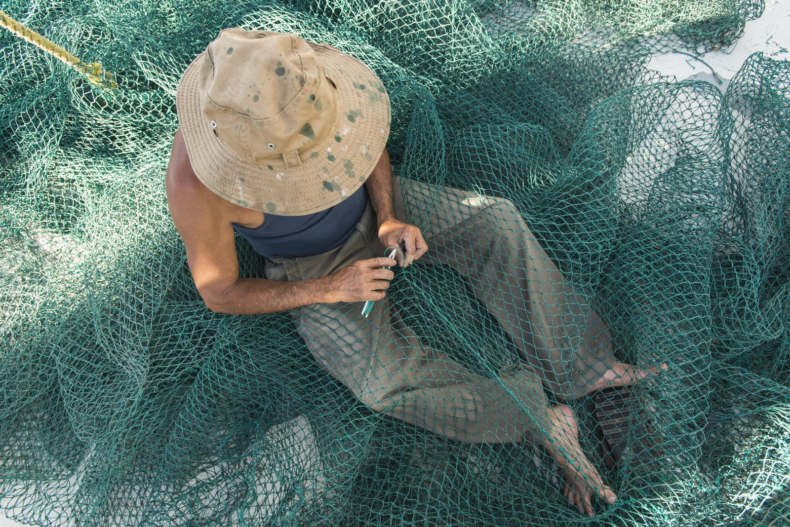 Vietnamese fisherman Dung Nguyen mends a shrimp net aboard a shrimp boat at the docks in Bayou La Batre, Alabama. The Nature Conservancy's Gulf of Mexico Program is a partnership among our five Gulf State Chapters to accomplish conservation across the entire Gulf ecosystem. The Gulf Program employs conservation professionals in Florida, Alabama, Mississippi, Louisiana, and Texas to restore and protect natural systems and natural areas across political boundaries. Photo credit: © Carlton Ward Jr.