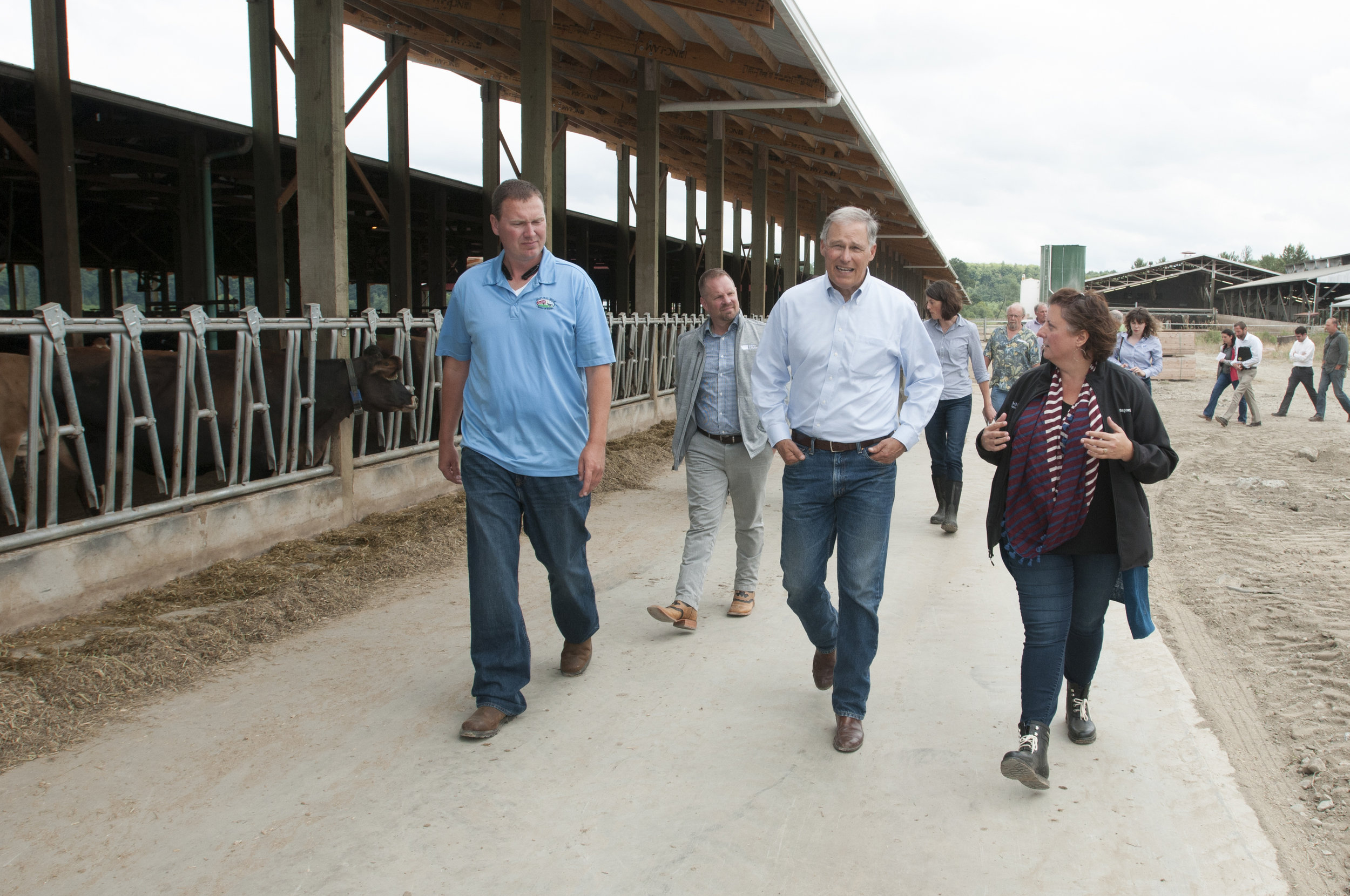 Jeremy Visser, left, gives Gov. Inslee, Jessie Israel and others a tour around the dairy farm. Photo by Hannah Letinich.