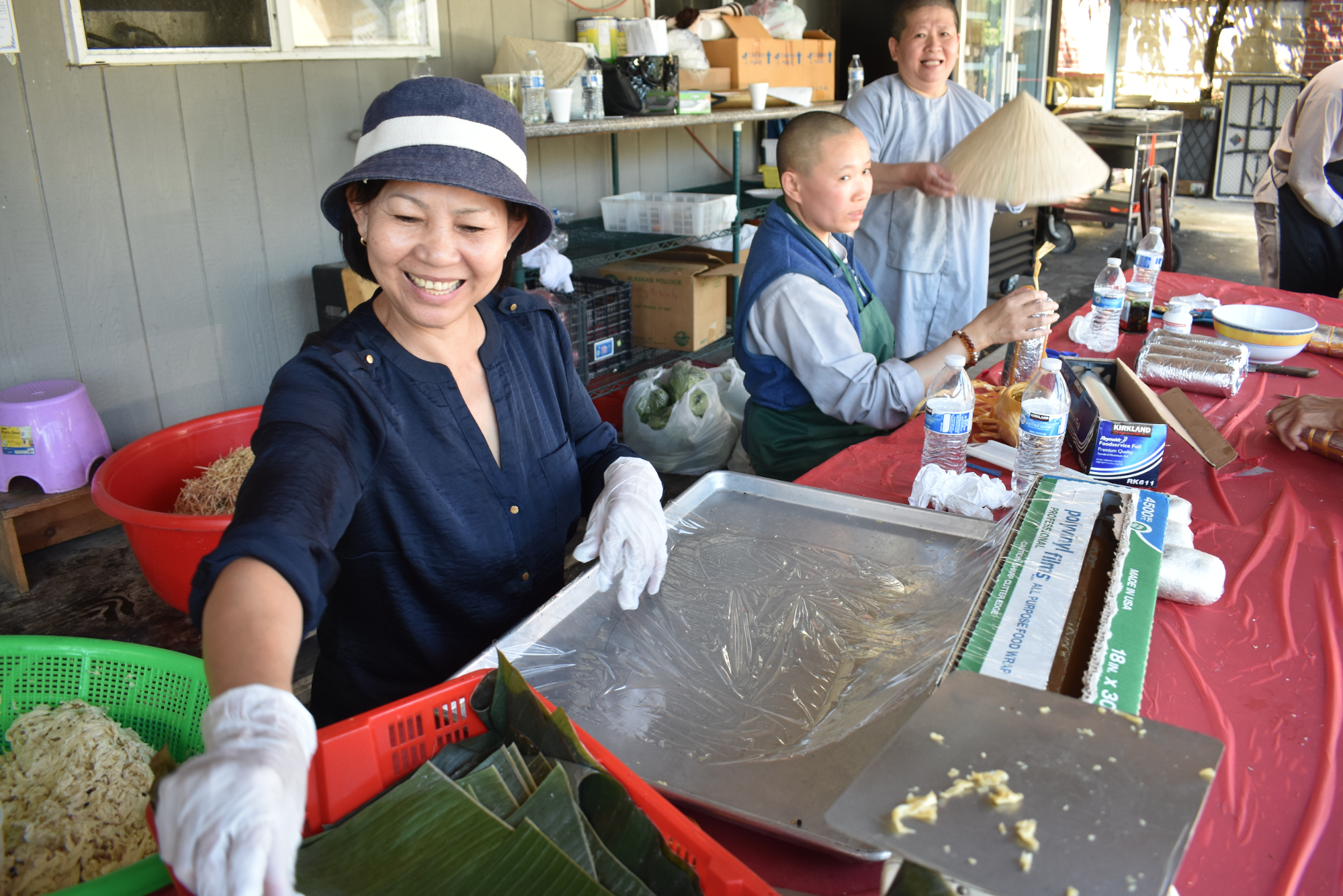 Volunteers and nuns preparing traditional Buddhist vegetarian ham rolls at the market stand.