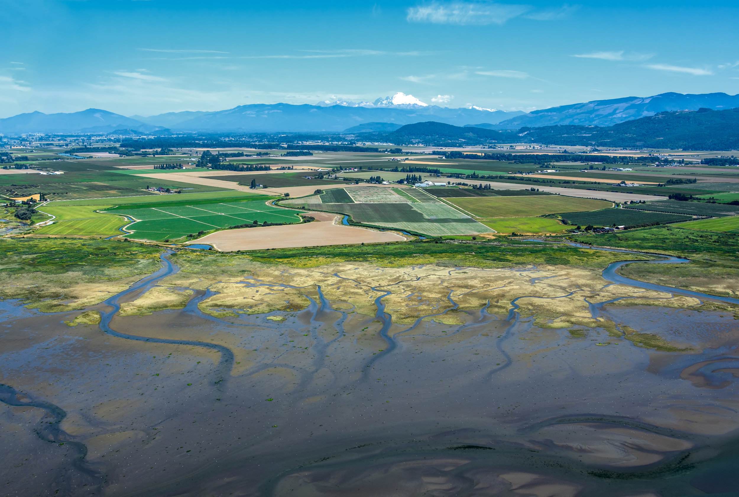 Aerial view of Skagit County's Fir Island farms and floopdplains, amongst the Cascade Mountains in the background. Photo  ©  Marlin Greene/One Earth Images