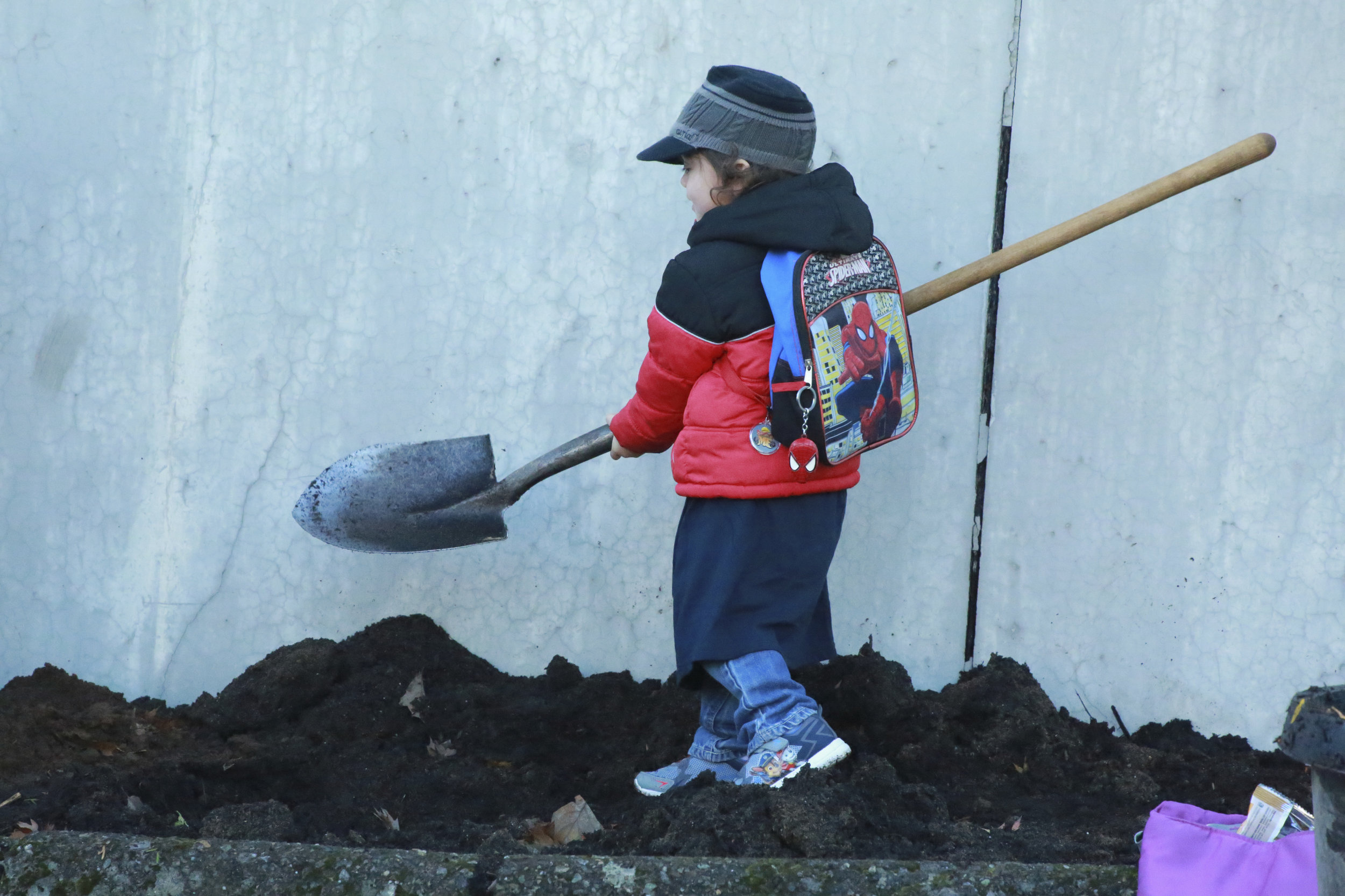 A young Depave Puget Sound volunteer helps move soil in the back lot of the Holy Rosary church and school in August. Photo © Marissa Singleton / TNC