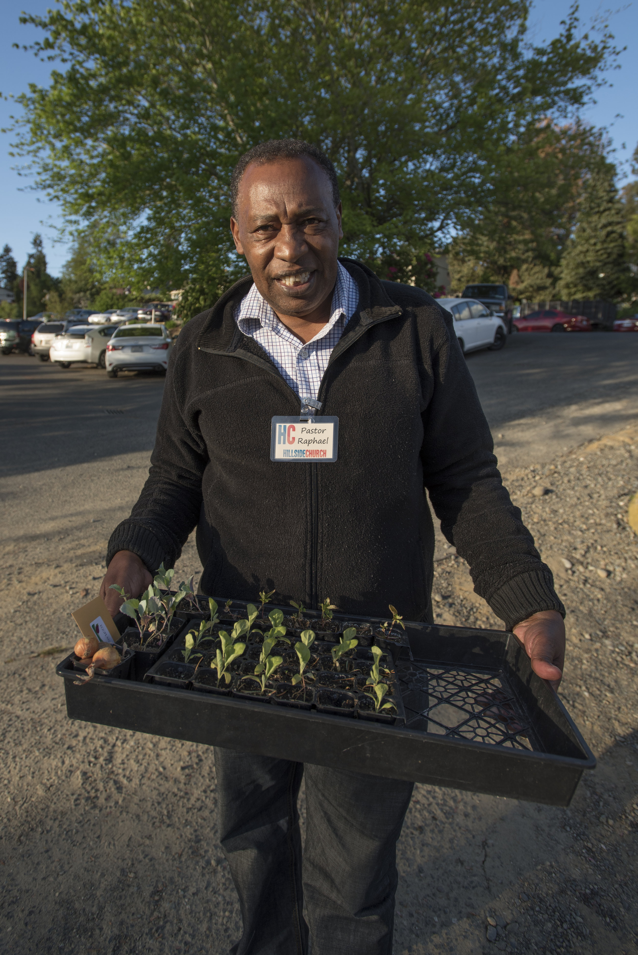 Pastor Raphael of Kent Hillside church holds a tray of plant starts. Photo © Hannah Letinich
