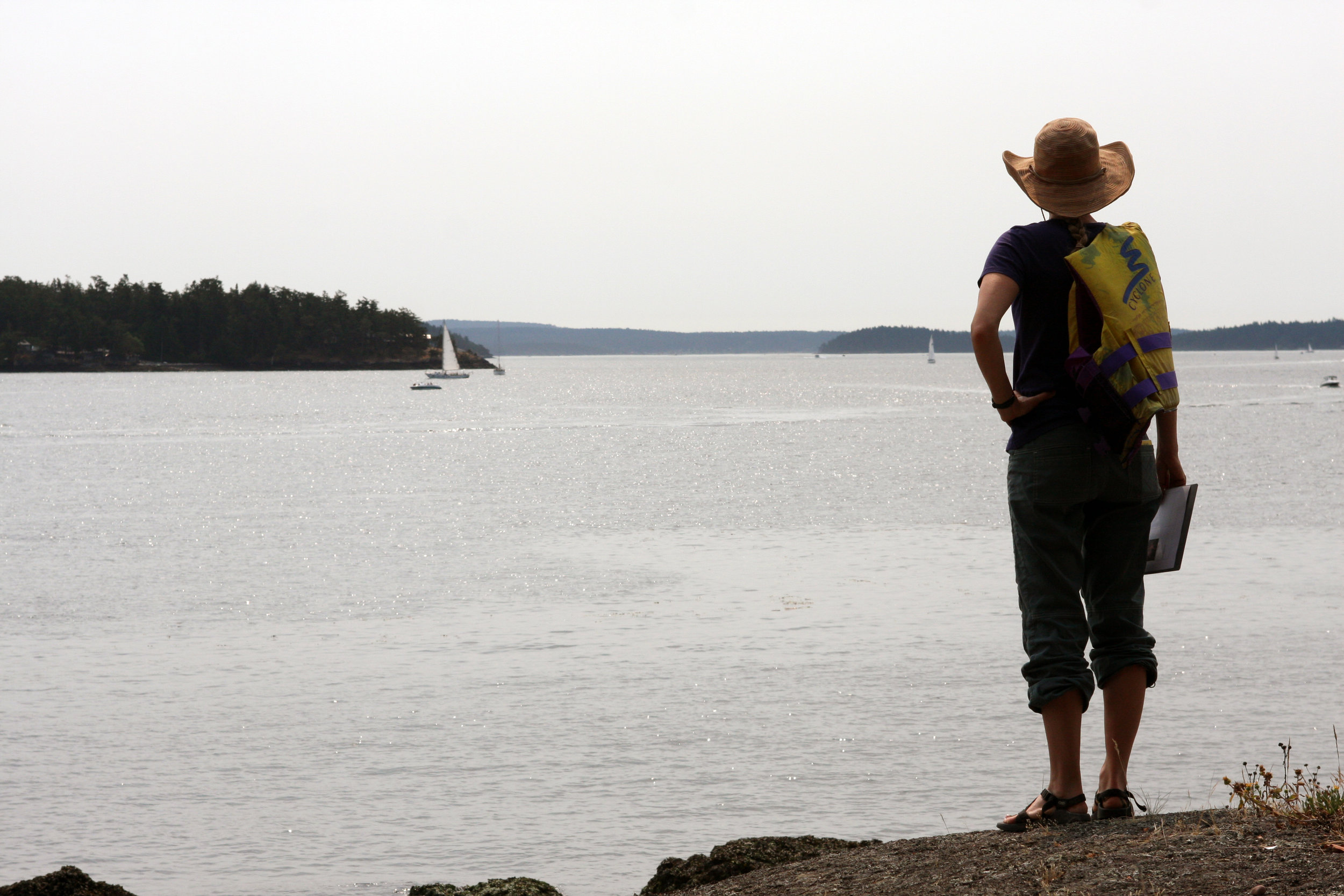 Ecologist Emily Howe looks out over Puget Sound during a survey of sea star health on Yellow Island. Photo by Heather Van Steenburgh.