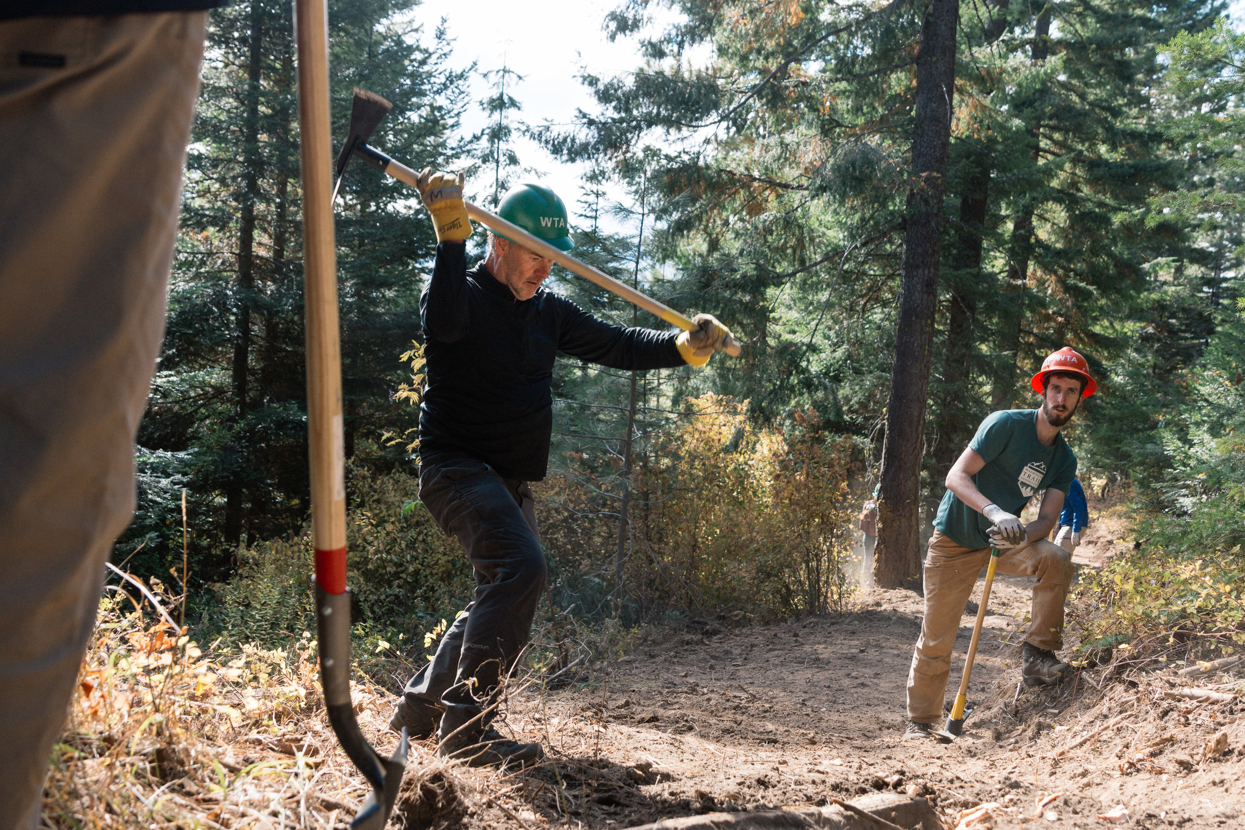 REI CEO Jerry Stritzke swings a tool while working on the first section of the new Towns to Teanaway trail system. Photo © Leslie Carvitto