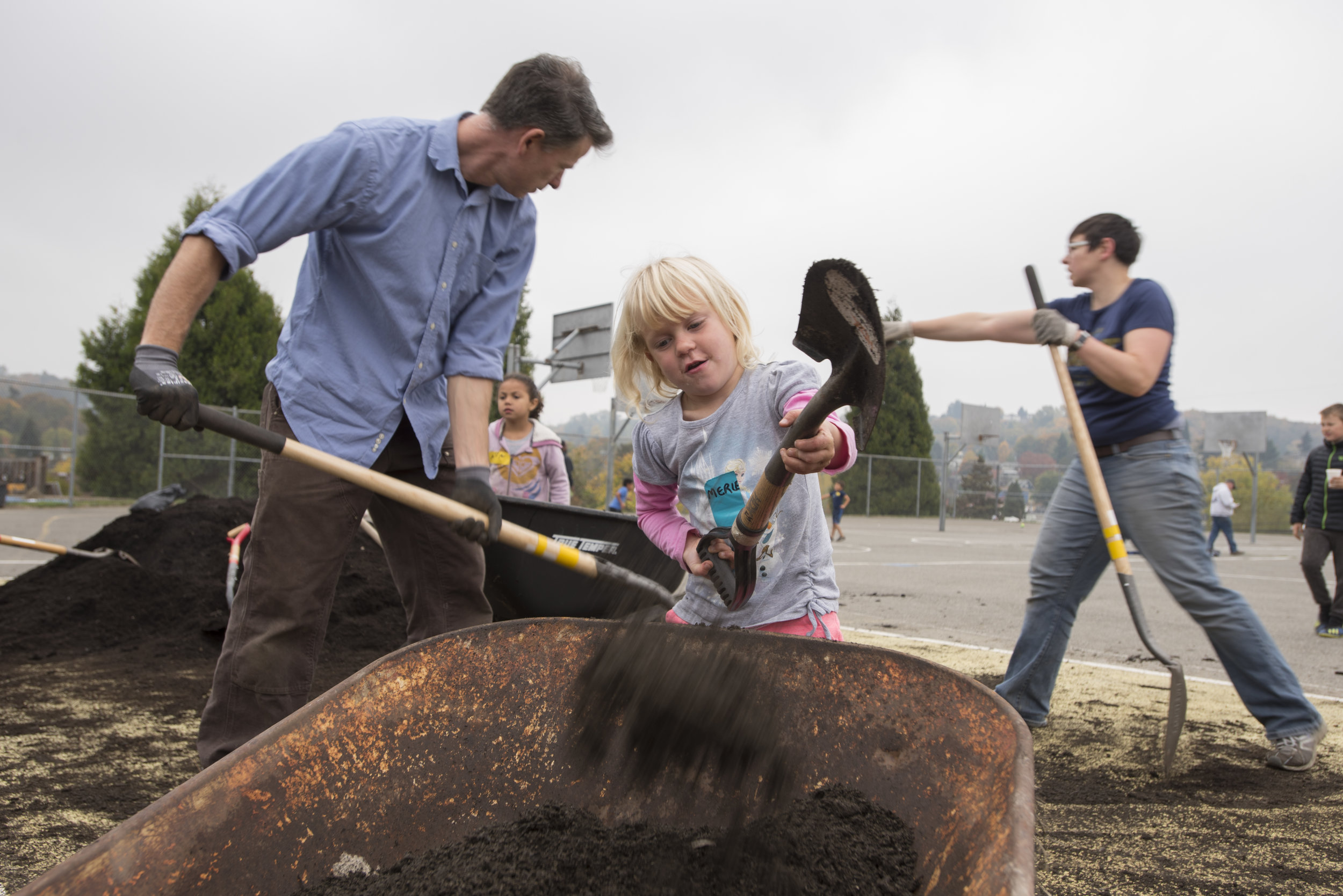A young girl dumps soil in a wheelbarrow at Hawthorne Elementary in October, 2018. © Hannah Letinich