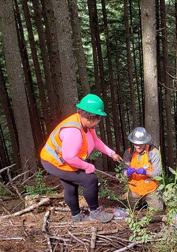 Dr. Tiara Moore (left), postdoctoral research associate, and Dr. Michael Case, forest ecologist, collect environmental DNA samples at Ellsworth Creek in SW Washington. Photo by Robin Stanton.
