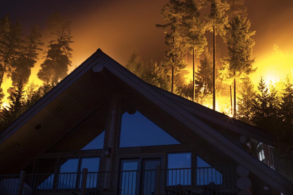 A fire burns near a home in Central Washington. © John Marshall